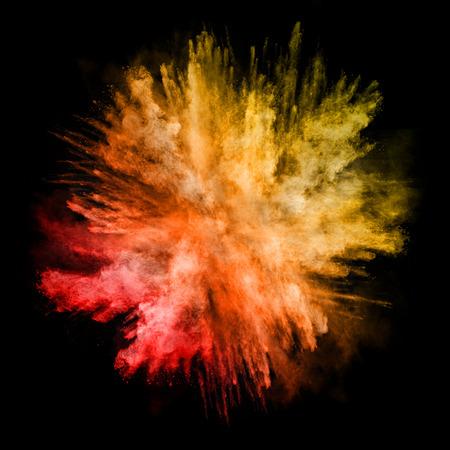 Explosie van gekleurd poeder, geïsoleerd op zwarte achtergrond Stockfoto