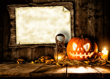 Scary halloween pumpkin on wooden planks with blank board. Empty space for text