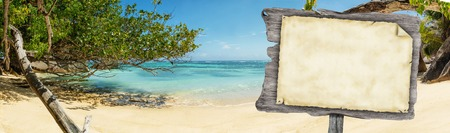 to and fro: Empty wooden board with old paper for copyspace placed on beautiful tropical beach at Seychelles. Concept fro travel and vacation