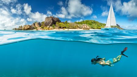 Giovane donna snorkeling vicino all'isola tropicale. Catamarano di ancoraggio sullo sfondo Archivio Fotografico - 64287822