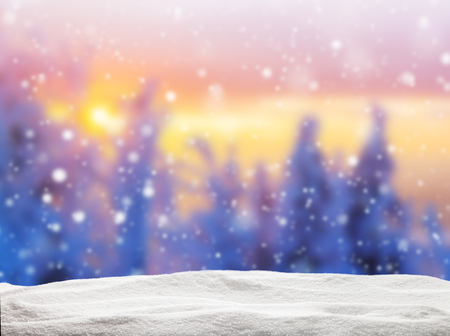 snowfalls: Abstract blur winter background with spruce forest in beautiful sunset. Pile of snow on background Stock Photo