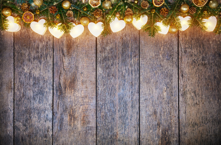 hearts background: Christmas colored lights with fir decoration placed on wood. Copyspace for text