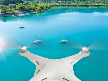 Drone flying above group of yacht anchoring next to lake shore