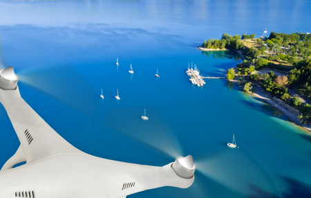 anchoring: Drone flying above group of yacht anchoring next to lake shore