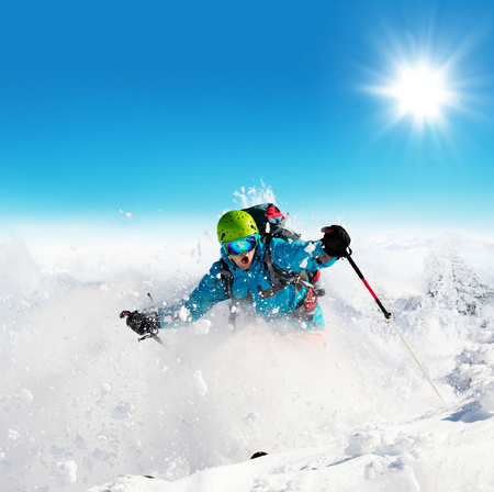 Freeride skier running downhill in freeze motion of snow powder. Stock Photo