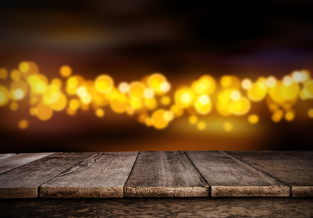 Blurred abstract golden spot lights isolated on black background. Empty wooden planks on background, ideal for product placement