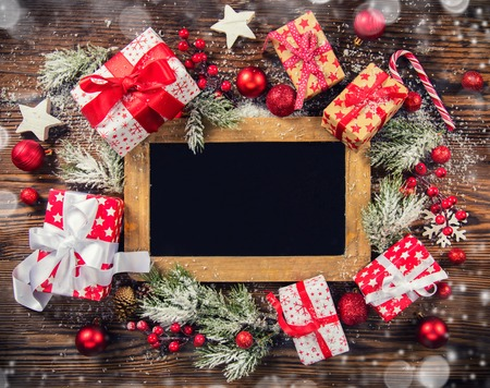 Christmas gift boxes with empty blackboard placed on wooden planks. Copyspace for text Stock Photo