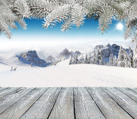 Empty wooden planks with winter alpine high mountains and spruce branches on top. Ideal for product placement