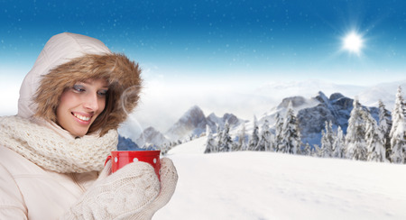 panoramatic: Beautiful winter portrait of young brunette woman drinking tea in the winter snowy scenery Stock Photo