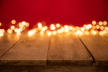 Blurred abstract golden spot lights on red background. Empty wooden planks on background, ideal for product placement