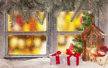 atmospheric: Vintage wooden window overlookhome interior with christmas tree. Decoration on foreground Stock Photo