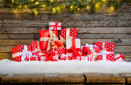 Christmas background with pile of gifts placed on wooden planks in snow. Fir decoration branches on top Stock Photo