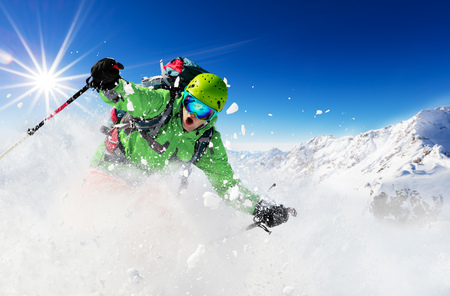 Freeride skieur avec sac à dos en descente en mouvement gel de la neige poudreuse.