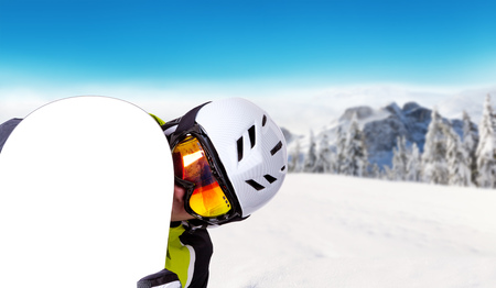 off piste: Snowboarder holding his snowboard off piste, beautiful winter landscape panorama on background