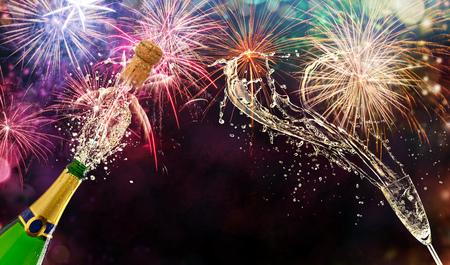 Fles champagne met glas over vuurwerkachtergrond. Vieringsconcept, vrije ruimte voor tekst