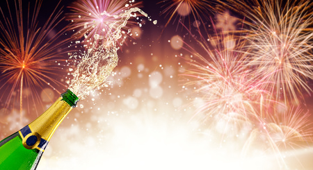 Splashing bottle of champagne over fireworks background. Celebration concept, free space for text