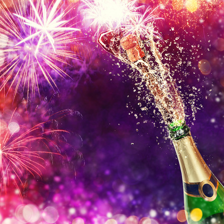colored bottle: Splashing bottle of champagne with glasses over blur colored background. Celebration concept, free space for text