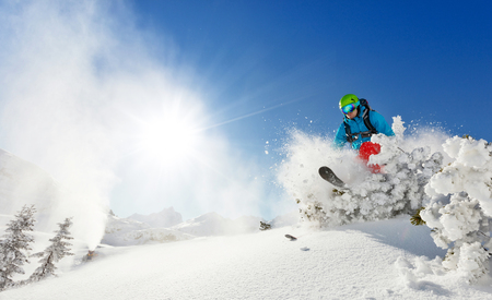 off piste: Freeride skier with rucksack running downhill in freeze motion of snow powder.