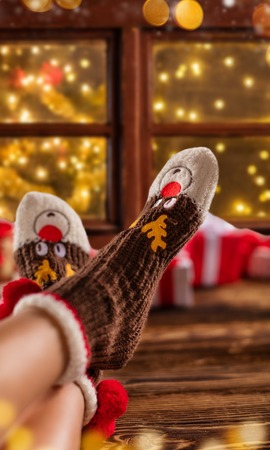 Detail of woman feet in woollen socks, blur Christmas tree on background