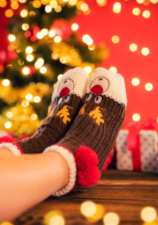 tree detail: Detail of woman feet in woollen socks, blur Christmas tree on background