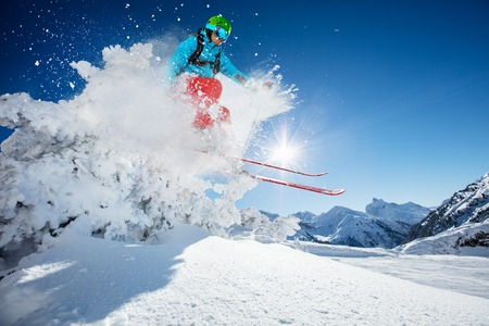 Freeride skier jumping from rock in freeze motion of snow powder. Stock Photo
