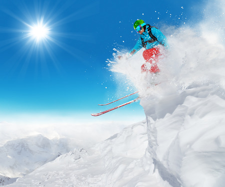 off piste: Freeride skier jumping from rock in freeze motion of snow powder. Stock Photo
