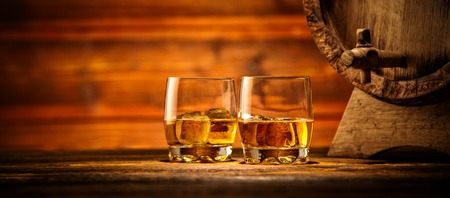 Two glasses of whiskey with ice cubes served on wooden planks with keg. Vintage countertop with highlight and a glass of hard liquor Stock Photo