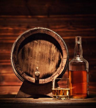 Bicchiere di whisky, bottiglia e barile con cubetti di ghiaccio servito su assi di legno con barile. Controsoffitto vintage con lumeggiatura e un bicchiere di superalcolici Archivio Fotografico - 67096575