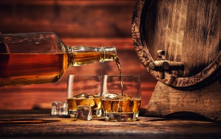 Pouring whiskey from bottle to two glasses with ice cubes, served on wooden planks. Vintage countertop with keg and glasses of hard liquor Reklamní fotografie