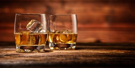 Dos vasos de whisky con cubitos de hielo servido en tablones de madera. encimera de la vendimia con el resalte y una copa de licor fuerte Foto de archivo - 67096574