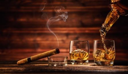 Het gieten van whisky van fles naar twee glazen met ijsblokjes, geserveerd op houten planken. Vintage aanrecht met hoogtepunt en een glas sterke drank
