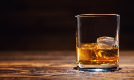Glass of whiskey with ice cubes served on wooden planks. Vintage countertop with highlight and a glass of hard liquor Stock Photo
