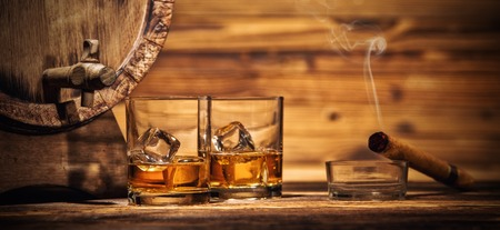 Two glasses of whiskey with ice cubes served on wooden planks with keg. Vintage countertop with highlight and glasses of hard liquor Stock Photo