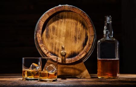 Dos vasos de whisky, botella y barril con cubitos de hielo que se presentan en tablas de madera con barril. encimera de la vendimia con el resalte y una copa de licor fuerte Foto de archivo - 67096583