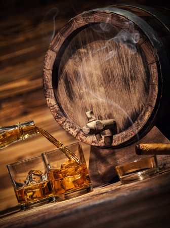 Pouring whiskey from bottle to two glasses with ice cubes, served on wooden planks. Vintage countertop with keg and glasses of hard liquor Stockfoto