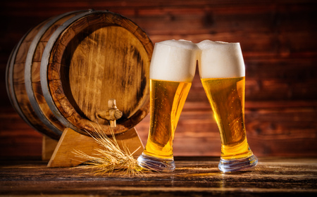 Two glasses of lager with old wooden keg, copyspace for text Stock Photo