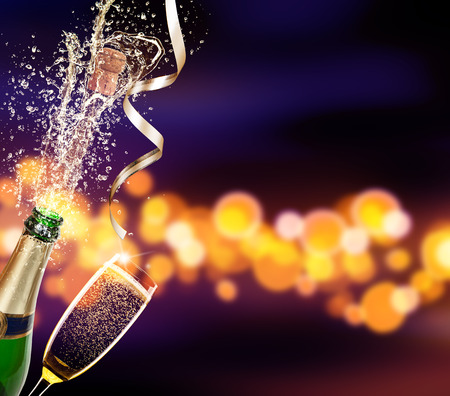 Splashing bottle of champagne with glass over blur colored spot background. Celebration concept, free space for text Stockfoto