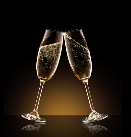 Two glasses of champagne with splash over black background. Celebration concept