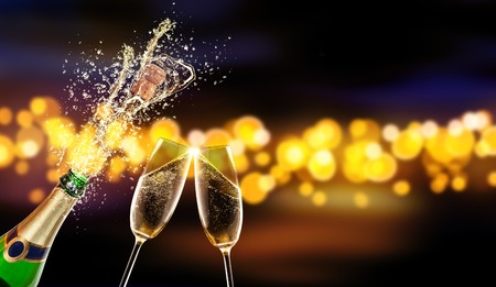 Splashing bottle of champagne with glass over blur colored spot background. Celebration concept, free space for text Foto de archivo