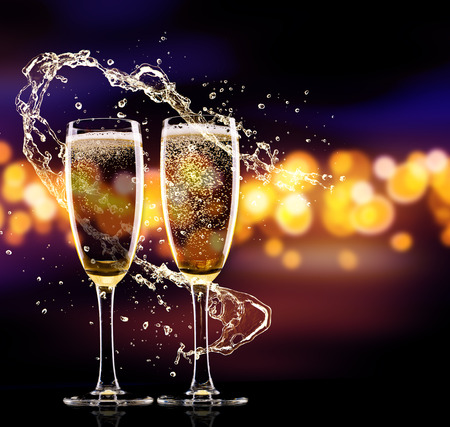 Two glasses of champagne with splash over blur spots lights background. Celebration concept, free space for text