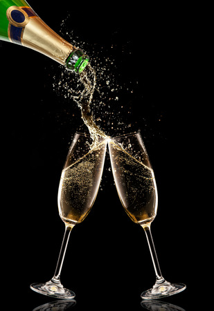 Pouring champagne wine into glasses over black background. Celebration concept