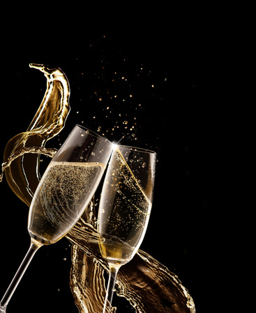 Two glasses of champagne with splash over black background. Celebration concept, free space for text
