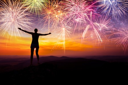 Silhouette of woman staying with stretched arms and watching the fireworks. Concept of New Year and celebration
