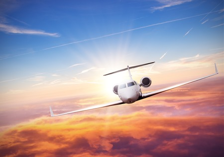 Private jet plane flying above clouds in beautiful sunset. Shot from front view. High resolution image