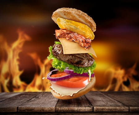 Maxi hamburger with flying ingredients placed on wooden planks with flames on background. Copyspace for text, high resolution image