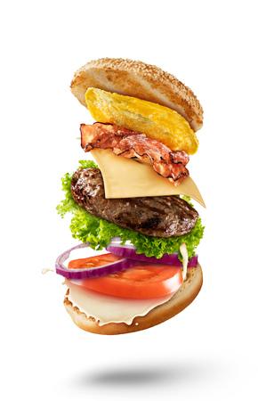 Maxi hamburger met vliegende ingrediënten op een witte achtergrond. Hoge resolutie