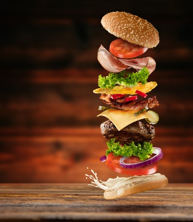 Maxi hamburger with flying ingredients placed on wooden planks. Copyspace for text, high resolution image Archivio Fotografico
