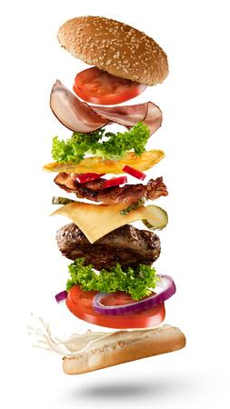 Maxi hamburguesa con ingredientes vuelo aislados en el fondo blanco. Imagen de alta resolución Foto de archivo - 68757541