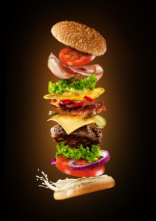 Maxi hamburger with flying ingredients isolated on dark background. High resolution image
