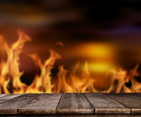 Old wooden table with flames on background, ideal for product placement. High resolution image